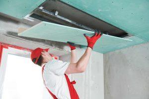 Gyprocker installing a plasterboard sheet in a bulkhead area.